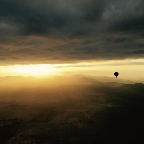 A Marrakech Hot Air Balloon flying under clouds with Atlas mountains view